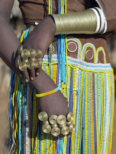 The finery of a Datoga woman. The traditional attire of Datoga women includes beautifully tanned and decorated leather dresses and coiled brass ornaments of every description.  Yellow and light blue are the preferred colours of the beads they wear.  Scarification of the face is not uncommon among women and girls.The Datoga (known to their Maasai neighbours as the Mang'ati and to the Iraqw as Babaraig) live in northern Tanzania. John Warburton-Lee Photography