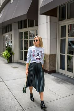 Laurie Young pairs her pleated skirt with a graphic printed sweater for an urban street style, combining both feminine and androgynous vibes for an overall winning look. Wear this outfit with patent Chelsea boots to steal Laurie's style! Metallic Skirt Outfit, Midi Skirt Outfit, Green Skirt Outfits, Green Pleated Skirt, Metallic Pleated Skirt, Khaki Skirt, Modest Fashion, Skirt Fashion, Fashion Outfits