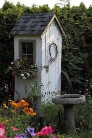 too cute!!!tiny garden shed..with alot of attention to details..so it doesn't look neglected..love the grapevine wreath..