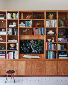The house was originally designed in 1953 for an artist, whose studio had this plywood wall unit, opposite, for storing supplies. Since the couple uses the area as a family room, they retrofitted it with lower cabinets for their daughter's games, a spot for a TV, and shelves up top for books and their favorite objects.: