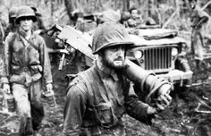 Gaunt, weary, hollow-eyed, machine gunner PFC George C. Miller carries his weapon to the rear after 19 days of heavy fighting while beating back the Japanese counterattack at Hill 660. This moving photograph was taken by Marine Corps combat photographer Sgt Robert R. Brenner.