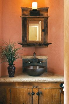 Côté built this corner cabinet in the main-floor powder room around an old mirrored door that he had been carrying around for years. The walls in this room and throughout the house are finished with a natural earth plaster that resembles stucco and will never need to be painted or touched up.