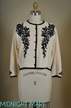 Vintage 1950s ivory lambswool cardigan with 3/4 sleeves, black satin trim, buttons, and seed bead beading on front, back neckline and sleeves. Side
