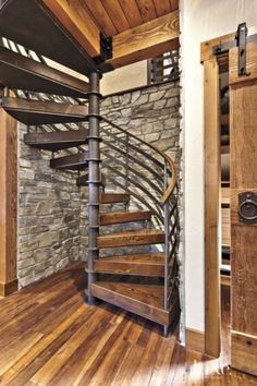 Exposed wood beams, a barn-style door from real Carriage door Company and stone walls surrounding the winding staircase— crafted by Ravenhill Construction—resonate with the home's setting. The Heritage Timber Ddition floors are from duChâteau.