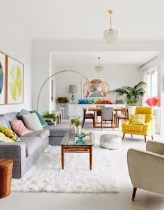 Gorgeous all white living room w/ just the right amount of fresh color pops. A gray couch, furry rug, and a yellow armchair make this space feel so comfy & cozy.