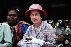 Queen Elizabeth II watching and photographing (with her gold Rollei camera) traditional dancers on October 27, 1982 in Funafuti in Tuvalu during the Royal Tour of the South Pacific.