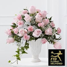 Turn your grief into a beautiful display of love and respect for the dearly departed. Deliver a gift of warmth and grace to the funeral or memorial, like this stunning combination of pink roses and carnations with delicate baby's breath, variegated ivy and vibrant greenery in a grand pedestal vase. This gorgeous arrangement expresses your wishes for peace and comfort during the saddest of occasions. Size is approximate.<br><br>Handmade & Delivered by Your FTD Florist.