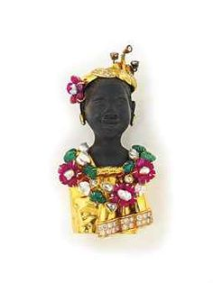 AN EBONY AND GEM-SET FIGURAL BROOCH -   Designed as a female bust with ebony head, diamond-set earrings, turban and dress, and emerald, ruby and freshwater cultured pearl flowerhead details, 9.0 cm