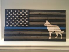 Show your appreciation to the K-9 Police Officer in your life with this hand painted Thin Blue Line Rustic American Flag. This flag is made of 23 boards hand painted in black and white with the symbolic thin blue line in the middle. Ready to hang with 2 d-hooks on the back on the flag.  I am able to customize these with last names, badge numbers or the dog name in the center of the blue line. The name or badge number would be cut from matte black vinyl and placed in the middle of the blue…