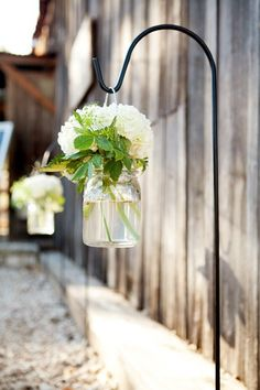 hanging arrangements lining walkways. Would be pretty with the tinted mason jars and flowers.