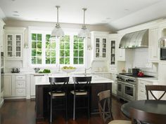 Crisp white cabinets, a white herringbone tile backsplash and white countertop create a bright and cheery backdrop in this family-friendly eat-in kitchen.