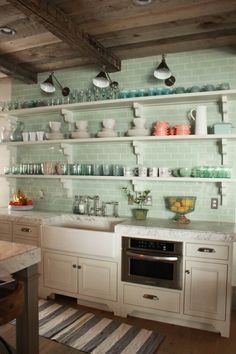 Love this turquoise backsplash with long open shelving with pretty dishes. The ceilings are perfect & those light fixtures are pretty awesome!