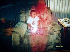 "Amanda sent us this wonderful ghost picture of a baby on grandpa's chair.  It's an older photo that was re-photographed with a camera instead of copying it via scanner (to get it on her computer).  Please disregard the white flash on the baby's legs, but consider the human form or apparition seemingly holding the infant:  ""My aunt's best friend gave birth to the baby boy in the picture, a few weeks after her father passed away. During a visit when the child was about six month"