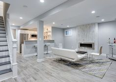 Modern basement living room with small kitchen porcelain tile floor and white furniture with fireplace