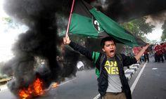 ผู้ประท้วงชาวอินโดนีเซียโบกธงและตะโกนต่อต้านการขึ้นราคาน้ำมันของรัฐบาล ที่หน้าอาคารรัฐสภาในเมืองเมดาน ทางเหนือของเกาะสุมาตรา หลังจากมีการคาดกันว่า รัฐบาลจะลดเงินอุดหนุนน้ำมันในงบประมาณก้อนใหม่...