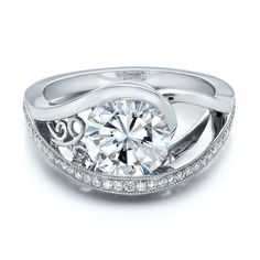 #100551 This stunning engagement ring features a round brilliant cut diamond tension set atop a wrapped platinum shank, with custom filigree and bright cut set diamond accents....