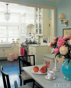 Gorgeous little cream colored kitchen with dark floors leading into a lovely light robin's egg blue breakfast room with perfect swing arm sconces. Adore how the marble from the kitchen countertops is repeated on the surface of the table in the next room. Simple and beautiful.