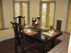 The family dining room is in the out-cove of the kitchen, and contains both a booth and antique chairs.