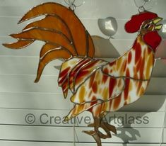 """rooster stained glass The 12"""" wide x 11"""" high colorful Stained Glass Rooster has flowing amber tail, brown feet, golden beak, a red comb on top of the rooster head and a red waddle under the rooster chin. - $42.95"""