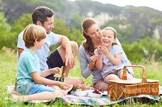 Shot of a young family enjoying a picnic on a sunny field - stock photo #1292343