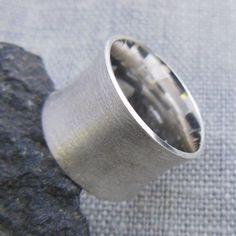 Dieser schön geschwungene, aber trotzdem sachlich wirkende Ring aus gebürstetem Silber ist modern und sportlich.  Der Ring ist fein mattiert und die Kanten sind poliert. Sie erhalten ihn in...