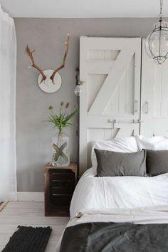 faire une tete de lit en portes blanches, linge de lit gris et blanc, parquet blanchi, couleur mur gris, deco murale bois de cerf, table de nuit en cagette de bois