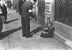 A Warsaw ghetto resident gives money to two children on a Warsaw ghetto street