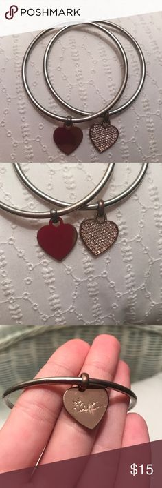 Michael Kors Bangles Two bangles bangle set. Rose gold plated but rose gold coming off and appears more of a silver and rose gold combo. Two heart charms, one is studded. They have scratches on them. Michael Kors written on back of studded heart charm as shown in third picture. Michael Kors Jewelry Bracelets