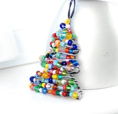 Handcrafted, wire-wrapped and beaded Christmas tree ornament is made with a combination of dark colored annealed steel and bright steel wire and