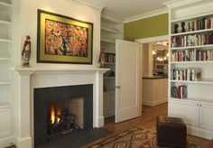 Had to pin this - it's the same colour green as my living room. Love the built ins (white with lower cupboards and open uppers) as well as the simple but classic fireplace design. I like the black surround with the white mantle. Slate Fireplace Surround, Tile Around Fireplace, White Fireplace Mantels, Classic Fireplace, Country Fireplace, Brick Fireplace Makeover, Fireplace Hearth, Fireplace Remodel, Fireplace Surrounds