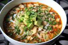 Tortilla soup recipe made with chicken or turkey, cilantro, onions, garlic, jalapeños, tomatoes, spices, stock, lime juice and served with cheese, tortilla chips, and avocado.