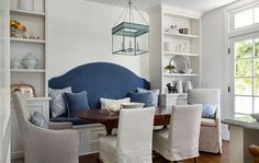 Cottage breakfast room boasts a built-in bench lined with a blue seat cushion and a blue curved upholstered back flanked by floor to ceiling shelving units facing an antique oval dining table surrounded by gray slipcovered dining chairs as well as white slipcovered side dining chairs illuminated by The Urban Electric Co Chisholm Hall Lanterns.