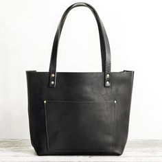 7ee9715d4620 A black leather tote with outside pocket and bridle leather handles Black  Leather Tote Bag