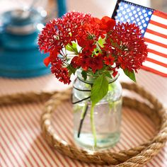 4th of July Flower Centerpiece-This fun 4th of July centerpiece takes just minutes to pull together. Fill a clear mason jar with fresh red, white, or blue flowers and add a miniature American flag to finish.