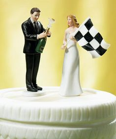 Bride at Finish Line with Victorious Groom Wedding Cake Topper made of hand painted porcelain. The bride is wearing an elegant white dress while holding a black and white checkered flag. The groom is wearing a handsome black suit, popping open a bottle of champagne.