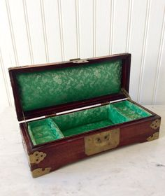 Beautiful footed wooden jewelry/ring box with green satin decorative lining. Hinged lid with inlaid carved hetian jade, brass engraved corners, clasp, & details. In very good vintage condition with a slight small stain on satin in middle compartment. Possibly could be cleaned & removed. Im not sure what kind of wood ( rosewood?). Shipped insured!  Measures 10 long x 4 wide x 3 height Thanks for shopping YellowHouseDecor!  Please visit my sisters shop for more vintage items ( ella...