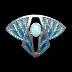 This is not contemporary - image from a gallery of vintage and/or antique objects. LEVINGER & BISSINGER  A silver and blue plique-a-jour brooch set with a central opal.