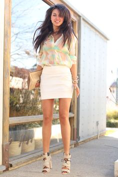 Minty fingernails, mint/lemon/coral color block blouse with miniskirt, toothy smile, straight chestlength dark chocolate hair, lightly tanned face & legs, creamy chunky-heeled sandals; shrubs & leafless tree reflected in window