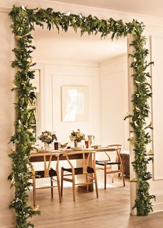 A doorway framed with a garland accented with silver and gold ornaments, welcomes guests to a Christmas dinner.