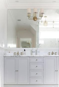 Stunning white and gray bathroom features white paint on top half of walls and marble tiles on bottom half of walls finished with a chair rail lined with a single gray bathroom vanity, divided into his and her sections, topped… Continue Reading → Grey Bathroom Vanity, Best Bathroom Vanities, White Bathroom, Master Bathroom, Gray Vanity, Bathroom Marble, Bathroom Cabinetry, Master Baths, Bathroom Photos