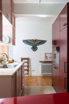 A light-pink kitchen with a marble countertop wraps the central lightwell, while a nearby cabinet island in dark pink houses appliances. Athens Apartment, Family Apartment, Green Plywood, Maine, Plywood Storage, Wooden Dining Tables, Dark Interiors, Apartment Interior Design, Kitchen Photos