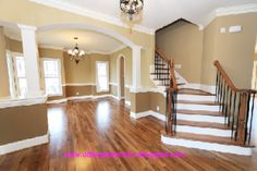 A picture of nice wood floors stair case foyer and dinning room. I like the two tone paint separated by the chair rail. I like the concept and look.