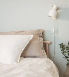 Natural linen pillowcases and a quilt cover in a bedroom with light green walls