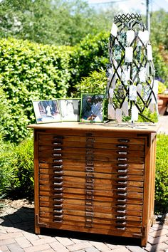 Love this wedding reception file cabinet table - holds escort cards (attached to vintage petticoat dryer) and photos of the bride and groom's parents on their wedding days (I did the same for our wedding).