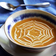 Spiderweb Pumpkin Curry Soup | Meals.com - Nothing screams Halloween like spiderweb soup! To get the look, pipe circles of sour cream onto the savory soup through a small cut in the corner of a plastic bag, then pull a toothpick or knife through the circles from the center to the edge of the bowl. #pumpkin #halloween