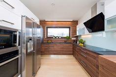 Kuchyň chtěla majitelka pojmout hlavně prakticky a jednoduše. Zajímavým prvkem je dřevěné obložení celé čelní stěny.