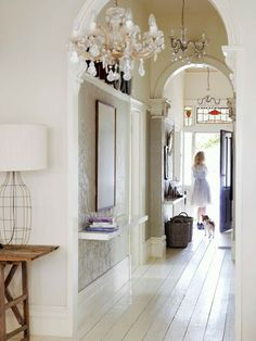 My entry hall is similar to this one as far as being narrow & I've been tempted in the past to add a shelf, like the one in this photo. The only thing that stops me is I can just imagine some poor kid coming to visit & running into it. Such a pretty space!
