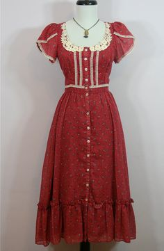 """Pretty cranberry colored peasant dress made by  Gunne Sax by Jessica, circa 1970s. Fabric is a semi sheer Voile, cotton blended with poly, printed with tiny polka dots and posies of flowers. Bodice has scoop neckline & puffed petal sleeves. Fastens with tiny buttons from top to bottom, on button band.  Sleeves, waistband and Bodice are trimmed with delicate lace and cotton crochet trims the neckline.Skirt gathers from waist and there is a 8"""" flounce at hem. Lined in acetate."""