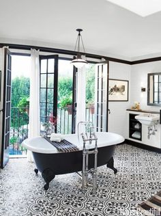 "BLACK AND WHITE BATHROOM Designer Deirdre Doherty designed this slightly industrial bathroom in an old Spanish Revival Los Angeles house. ""I wanted to do something that felt as if it could have been here forever — but with a little edge,"" she says."