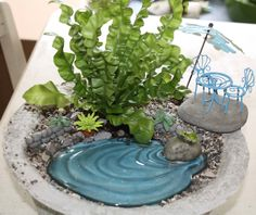 A container fairy garden in a home made papercrete planter with products from fairygarden.ca and some DIY items by Marthe Hook The plant is one of my favorites for container fairy gardening -Japanese Asplenium nidus fern aka Crispy Wave